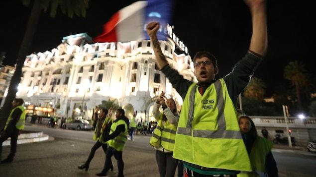 Un homme avec un gilet jaune lève les bras. Derrière lui, une femme avec un gilet jaune tient un drapeau français, et d'autres gens marchent dans la rue.