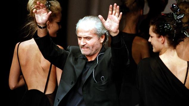 Gianni Versace saluer la foule lors d'un défilé de mode, en 1996.
