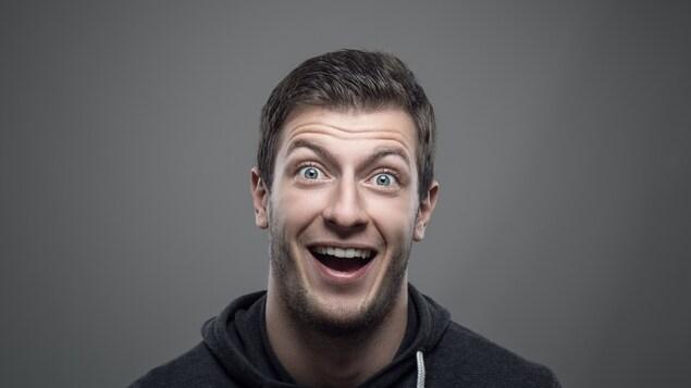 Un homme blanc fait une mine surprise à la caméra.