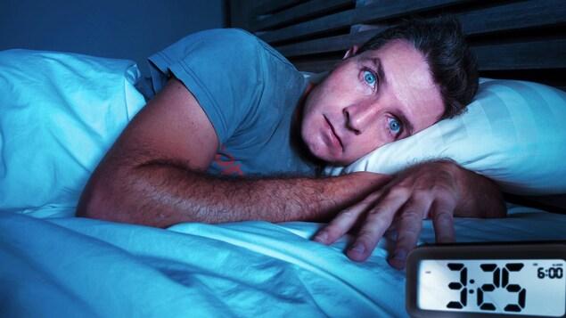 Un homme les yeux grand ouverts est couché sur le côté. Une horloge marquant 3:25 est près de sa main.