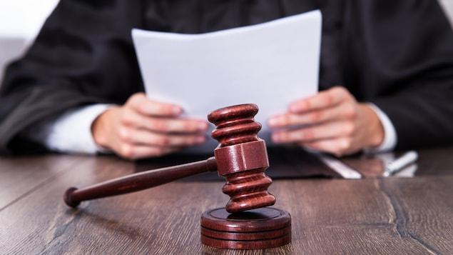 Un juge tient un document derrière son maillet