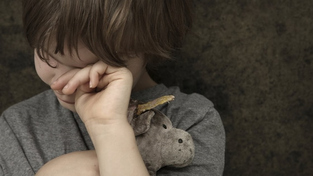 Un enfant essuie ses yeux en serrant un animal en peluche.