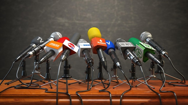 Des microphones de différents médias disposés sur un podium.