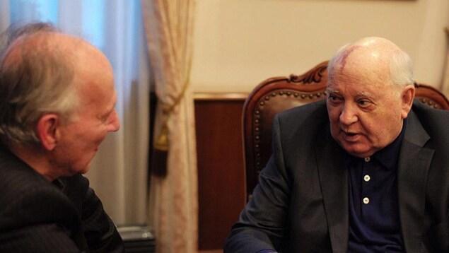 Deux hommes assis dans une pièce discutent.
