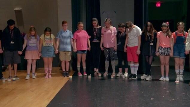 Des adolescents se tiennent la main, les yeux fermés et la tête penchée en recueillement, sur cette image tirée du documentaire <i>Song of Parkland</i>.