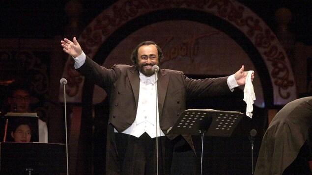 Luciano Pavarotti, sur scène, les bras tendus et tenant un mouchoir dans la main gauche.