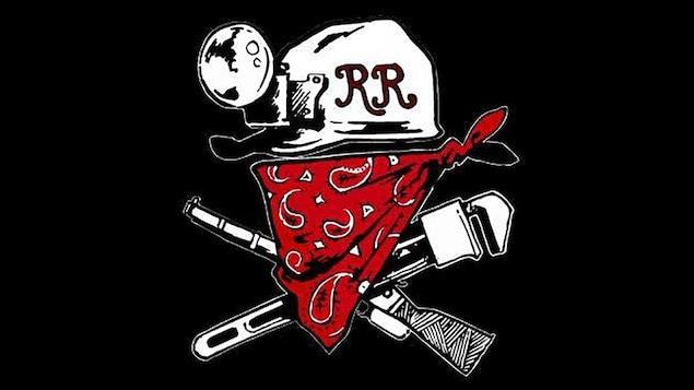 Le logo de Redneck Revolt, un groupe armé d'extrême gauche,  montre la tête d'un individu masqué, portant un casque de mineur, avec une carabine et une clé anglaise formant un « x » derrière.