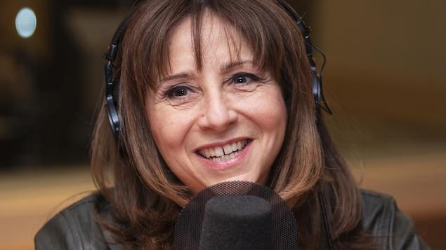 Nathalie Roy, avec des écouteurs sur la tête, parle devant un micro.