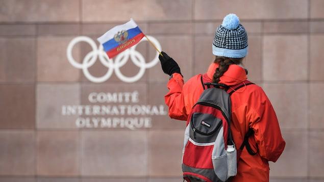 Une femme agite un drapeau de la Russie devant le quartier général du Comité international olympique à Pully, en Suisse.
