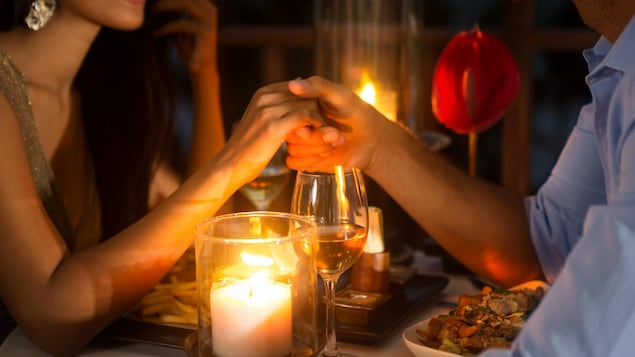 Un couple partage un repas romantique autour de bougies et d'une rose.