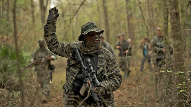 Des membres d'une milice survivaliste, le North Florida Survival Group, patrouillent dans la forêt, vêtus de vêtements de camouflage et armés de fusils.
