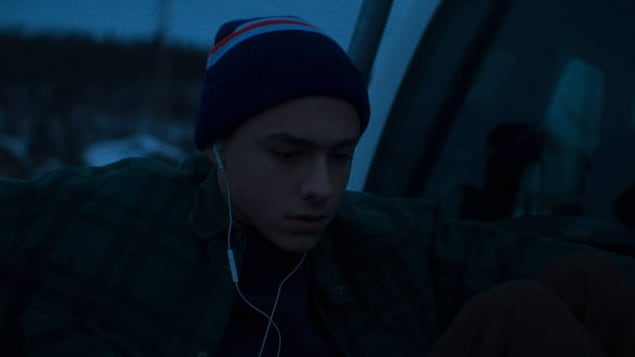 Un adolescent  portant une tuque portant des écouteurs dans les oreilles.