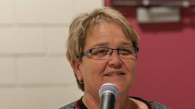 Le portrait d'une femme souriante avec un micro devant elle.