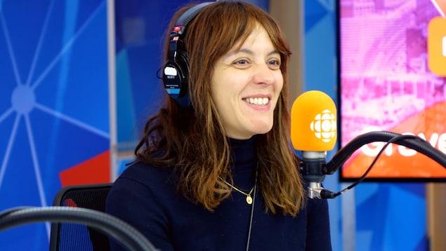 La comédienne et réalisatrice sourit devant un micro orange en regardant vers la droite.