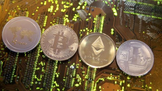 Monnaies virtuelles Ripple, Bitcoin, Etherum et Litecoin sur une carte mère d'un ordinateur.