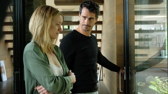 Un jeune couple (Laurence Leboeuf et Patrick Hivon) devant une porte vitrée.