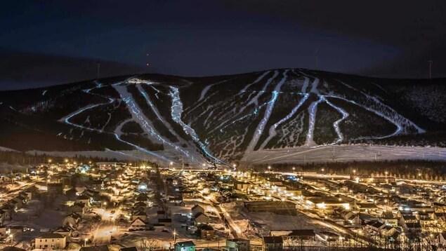 Un village éclairé au pied de montagne avec des pistes de skis lumineuses.