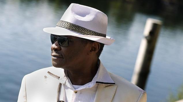 Mory Kanté porte un chapeau blanc et des lunettes de soleil.