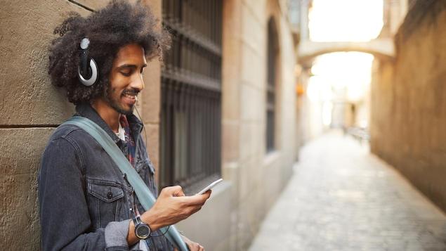 Un homme écoute un balado dans une ruelle.
