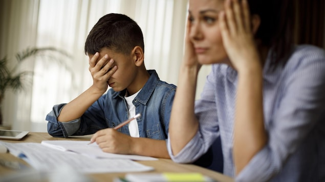 Une mère est impatiente avec son enfant qui fait ses devoirs.