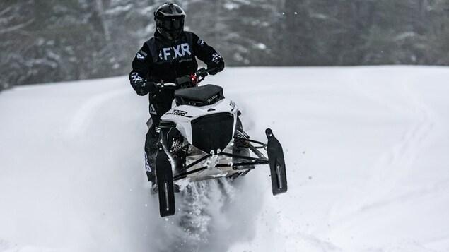 Une motoneige flottant à pleine vitesse sur la neige.