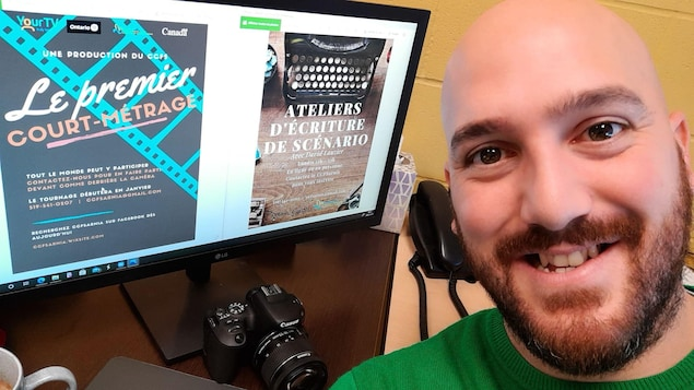 Un homme avec un chandail vert devant son écran d'ordinateur