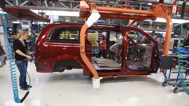 Le châssit d'une voiture en construction avec trois personnes qui installent des pièces dans l'usine Fiat-Chrysler de Windsor.