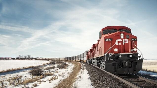 Un train de marchandises du CP circule sur des rails qui traversent un champ enneigé sur fond de ciel bleu.
