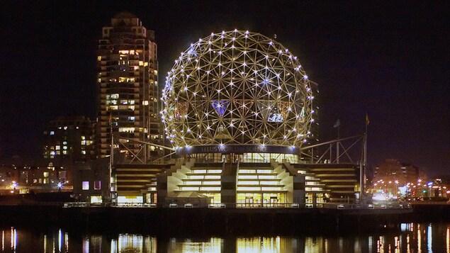 La structure en forme de boule du musée est illuminée et se reflète dans l'eau de la rivière la nuit.