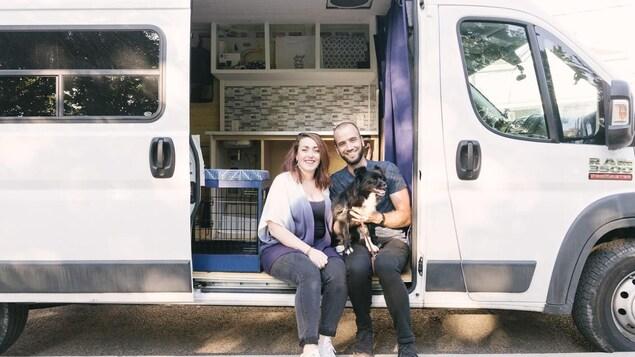 Myriam, Tanguy et Philibert le chien assis à l'extérieur de leur fourgonnette, porte ouverte, on aperçoit l'intérieur aménagé.