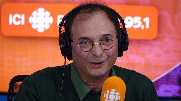 Normand Baillargeon derrière un micro dans un studio radio de Radio-Canada.
