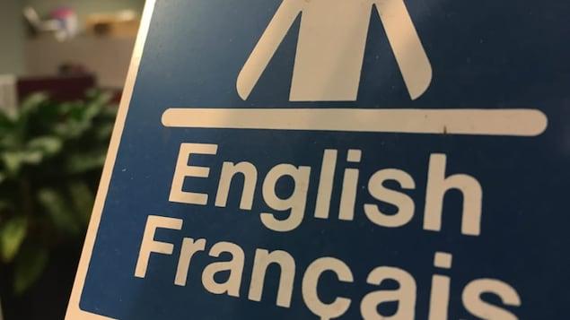 Affiche annonçant des services bilingues.