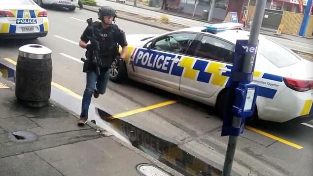 Un policier court avec une arme longue à la main.