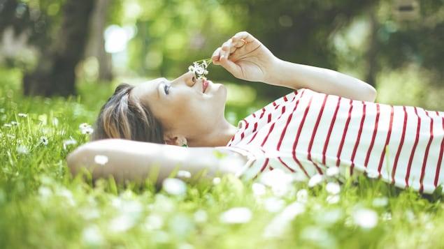 Une femme souriante couchée dans le gazon en train de sentir des fleurs qu'elle tient dans sa main.