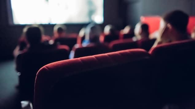 Des gens regardent un film dans une petite salle de cinéma.