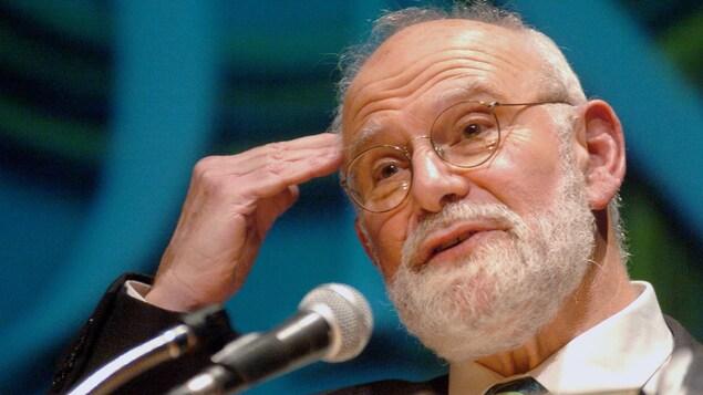 Un homme aux cheveux et à la barbe blanches parle devant un micro en portant une main à son front.