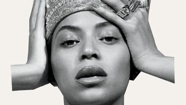 Visage de Beyoncé en noir et blanc. Elle porte une tiare et des grosses bagues. Elle se tient la tête à deux mains.