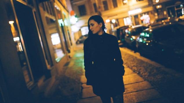 Une jeune femme marche avec inquiétude dans la rue le soir.