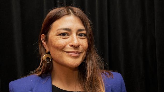 Portrait d'Elisapie Isaac sur fond noir. Elle porte un veston bleu, des boucles d'oreilles dorées et sourit à la caméra.