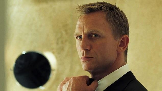 Portrait rapproché de Daniel Craig dans le rôle de James Bond. La tête légèrement tournée, il replace son noeud papillon avec ses mains.