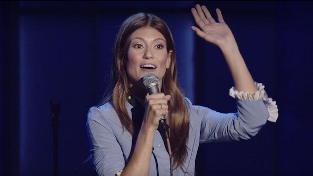 L'humoriste Katherine Levac, sur scène avec un micro dans la main droite et le bras gauche en l'air.