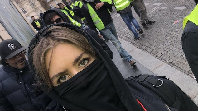 Lydia Képinski, masquée d'un foulard noir, dans les rues de Paris devant des hommes en gilets jaunes.