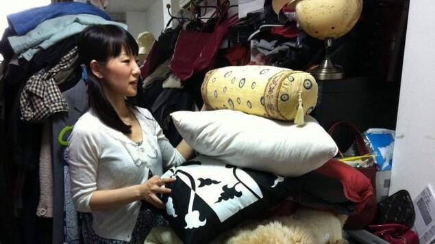 Marie Kondo, l'air ébahi, devant une immense pile d'objets.