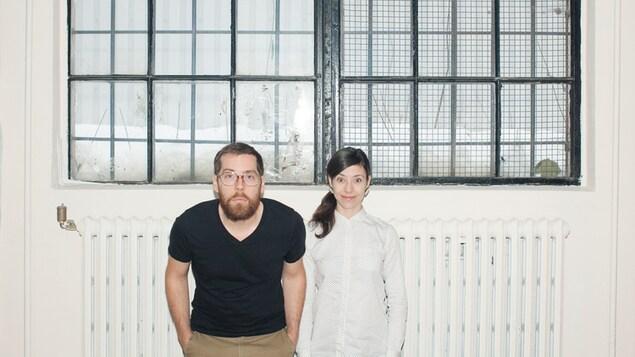 Simon Rivest et Catherine Lepage font une moue cocasse devant un mur blanc, au centre duquel une fenêtre de type industrielle laisse deviner un paysage hivernal.