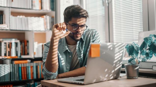 Un jeune homme assis à une table devant un écran d'ordinateur.