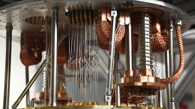Une photo d'un ordinateur quantique, composé de câbles cuivrés et de petits fils d'aluminium tendus entre deux plaques métalliques.