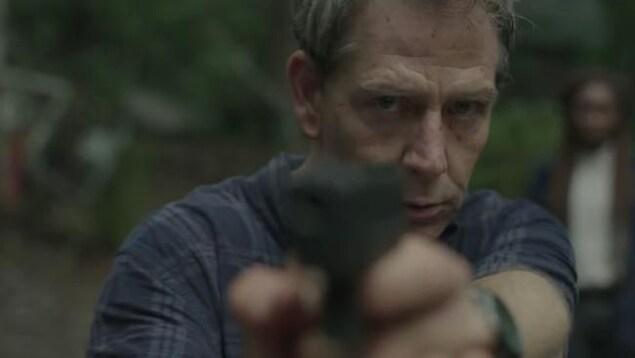 Un homme blanc dans la cinquantaine pointe un revolver dans notre direction.