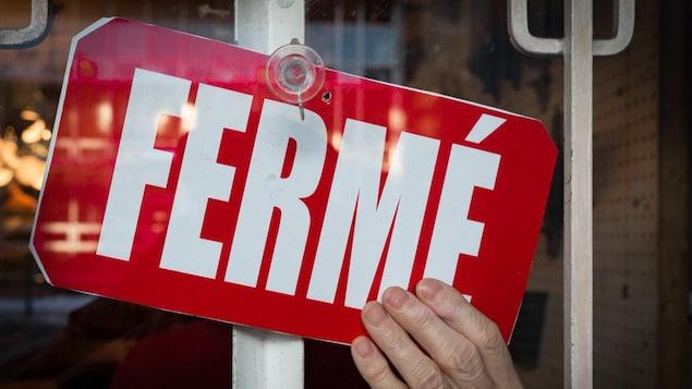 Une affiche « Fermé » dans la porte d'un commerce.