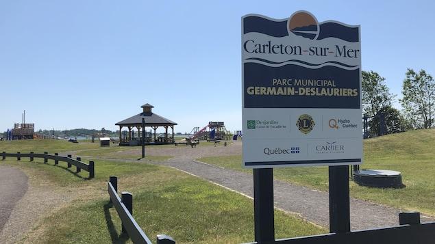 Une affiche du parc municipal Germain-Deslauriers et des modules de jeux en arrière-plan.