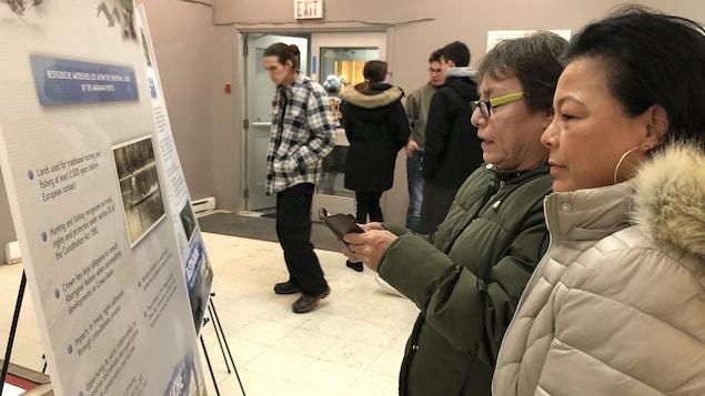 Deux Micmacs regardent des panneaux d'information